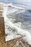 Energetic sea waves rolling on to the quay Stock Image