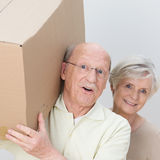 Energetic senior couple moving home. Energetic attractive senior couple moving home carrying out a cardboard box together and laughing at the camera, closeup of stock photo