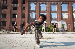 Energetic street dancer lunging at the camera. Happy energetic African American street dancer lunging at the camera with a cheeky smile as he performs his hip royalty free stock photo