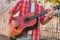 Energetic street musician granting song on street. Another song. Close up of appealing male hands rising guitar and picking strings stock photos