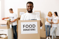 Energetic strong guy carrying a box with donations Stock Images