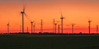 Energetic Sunset - Wind Energy. Image of spinning wind turbines and power lines at sunset in a field in Beauce the main agricultural region of France. Wind is an Stock Photo