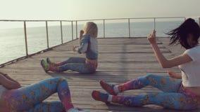 Energetic twerk by trendy teen girls on a wooden pier near the sea stock video footage