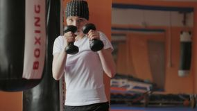 An energetic woman in boxing in the gym, coaches in dumbbells. 4k stock photos