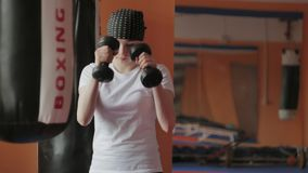 An energetic woman in boxing in the gym, coaches in dumbbells. 4k stock image