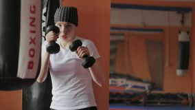 An energetic woman in boxing in the gym, coaches in dumbbells. 4k stock photo
