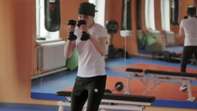 An energetic woman in boxing in the gym, coaches in dumbbells. 4k royalty free stock photography
