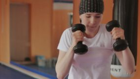 An energetic woman in boxing in the gym, coaches in dumbbells stock photography