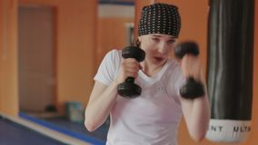 An energetic woman in boxing in the gym, coaches in dumbbells stock image
