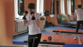An energetic woman in boxing in the gym, coaches in dumbbells stock photo