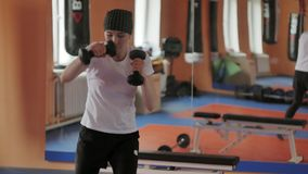 An energetic woman in boxing in the gym, coaches in dumbbells. 4k royalty free stock images