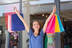 Energetic woman handing shopping bags Royalty Free Stock Images