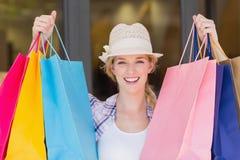 Energetic woman handing shopping bags Royalty Free Stock Image