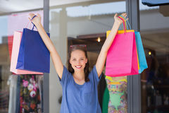 Energetic woman handing shopping bags Royalty Free Stock Photo