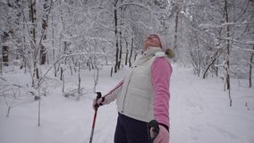 Energetic woman having nordic exercising in the forest.Happy female athlete standing with ski poles on the path in stock footage