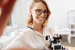 Energetic woman taking selfie with robot indoors Stock Photography