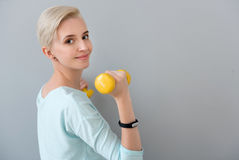 Energetic woman training with dumbbells. Sport is a power. Energetic healthy young woman looking at the camera while doing some exercises with dumbbells isolated Royalty Free Stock Image