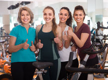 Energetic women riding stationary bicycles Stock Photo