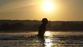 Hilarious man beats the lake water to entertain at sunset in slo-mo. An energetic young man beats the lake water with his hand to entertain and to make brilliant stock video