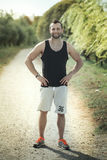 Energetic young man do exercises outdoors and running in park to Royalty Free Stock Photo