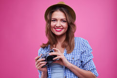 Energetic young woman with a camera over pink background Royalty Free Stock Image