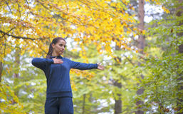 Energetic young woman do exercises outdoors in park to keep their bodies in shape. Fitness concept. Body-building theme. Sport mood stock image
