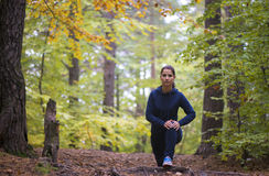 Energetic young woman do exercises outdoors in park to keep their bodies in shape. Fitness concept. Body-building theme. Sport mood stock photo