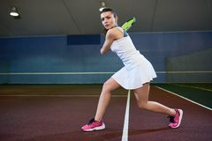 Energetic Young Woman Playing Tennis royalty free stock photo