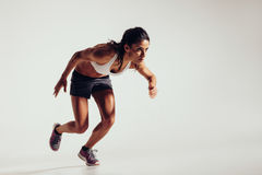 Energetic young woman running Stock Photo