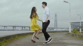 Happy boy and girl dance happily some speedy boogie on a pier on a sea coast stock video