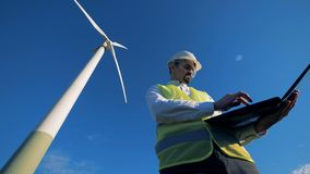 Energeticsexperten navigerar hans dator, medan stå nära en väderkvarn Förnybar alternativ energi, miljö stock video