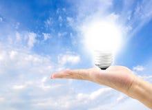 Energetyczna skuteczna żarówka w ręce z niebieskim niebem w tle Obrazy Stock