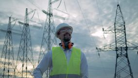 Energetyka pracownik jest uśmiechnięty po phonecall podczas gdy stojący blisko elektryczność linii zbiory