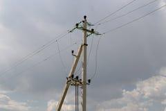 Energi och teknologi: den elektriska stolpen vid vägen med kraftledningen kablar, transformatorer mot ljus blå himmel som ger kop Arkivbild