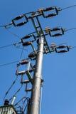 Energi och teknologi: den elektriska stolpen vid vägen med kraftledningen kablar, transformatorer mot ljus blå himmel som ger kop Fotografering för Bildbyråer