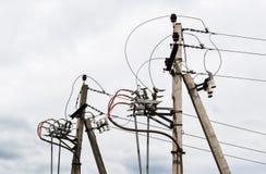 Energi och teknologi: Två elektriska poler med kraftledningen kablar, transformatorer på en bakgrund för molnig himmel Arkivfoto