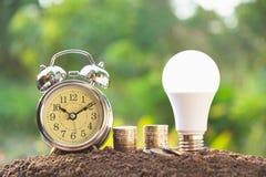 Energi - sparande ljus kula och ringklocka på buntar av mynt på n royaltyfria bilder