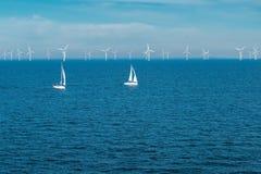Energia alternativa - fileira das turbinas e?licas e dos iate a pouca dist?ncia do mar no mar, geradores verdes do moinho de vent imagens de stock