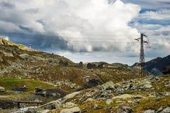 Energia elettrica nelle alpi con il cielo drammatico Fotografia Stock