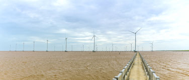 Energia limpa, planta de energias eólicas com um caminho às turbinas eólicas gigantes no mar Foto de Stock