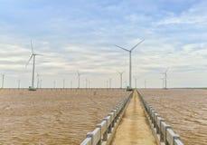 Energia limpa, planta de energias eólicas com um caminho às turbinas eólicas gigantes no mar Fotos de Stock Royalty Free
