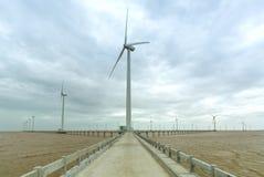 Energia limpa, planta de energias eólicas com um caminho às turbinas eólicas gigantes no mar Imagens de Stock Royalty Free