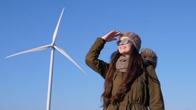 Energia renovável, menina exaltada em vidros que olham fixamente na distância no fundo das turbinas eólicas e céu filme