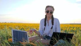 Energia renovável, menina que fala no portátil usando a bateria solar no campo dos girassóis, jovem mulher posta pela célula sola video estoque