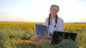 Energia słoneczna, dziewczyna chwyty w ręki słonecznej baterii na polu słoneczniki, młoda kobieta zasila laptop od panel słoneczn zbiory