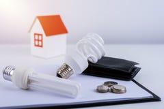 Energia - savings lampowi z portflem i monetami, papieru domu model Zdjęcia Royalty Free