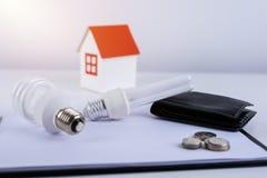Energia - savings lampowi z portflem i monetami, papieru domu model Obrazy Royalty Free