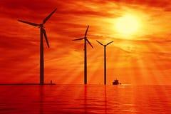 Energias eólicas sob o por do sol Foto de Stock Royalty Free