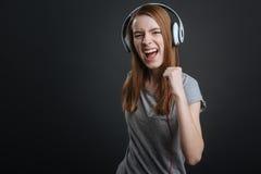 Energiczna ładna dziewczyna jest ubranym nowych hełmofony Obraz Stock