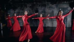 Energiczne młode dziewczyny w czerwonych dancingowych kostiumach perfoming grupowego tana w studiu z czarnymi ścianami zbiory